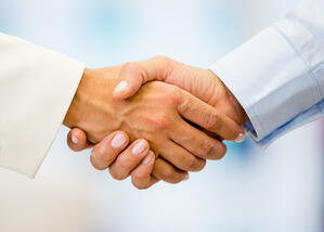 Business handshake closing a deal at the office