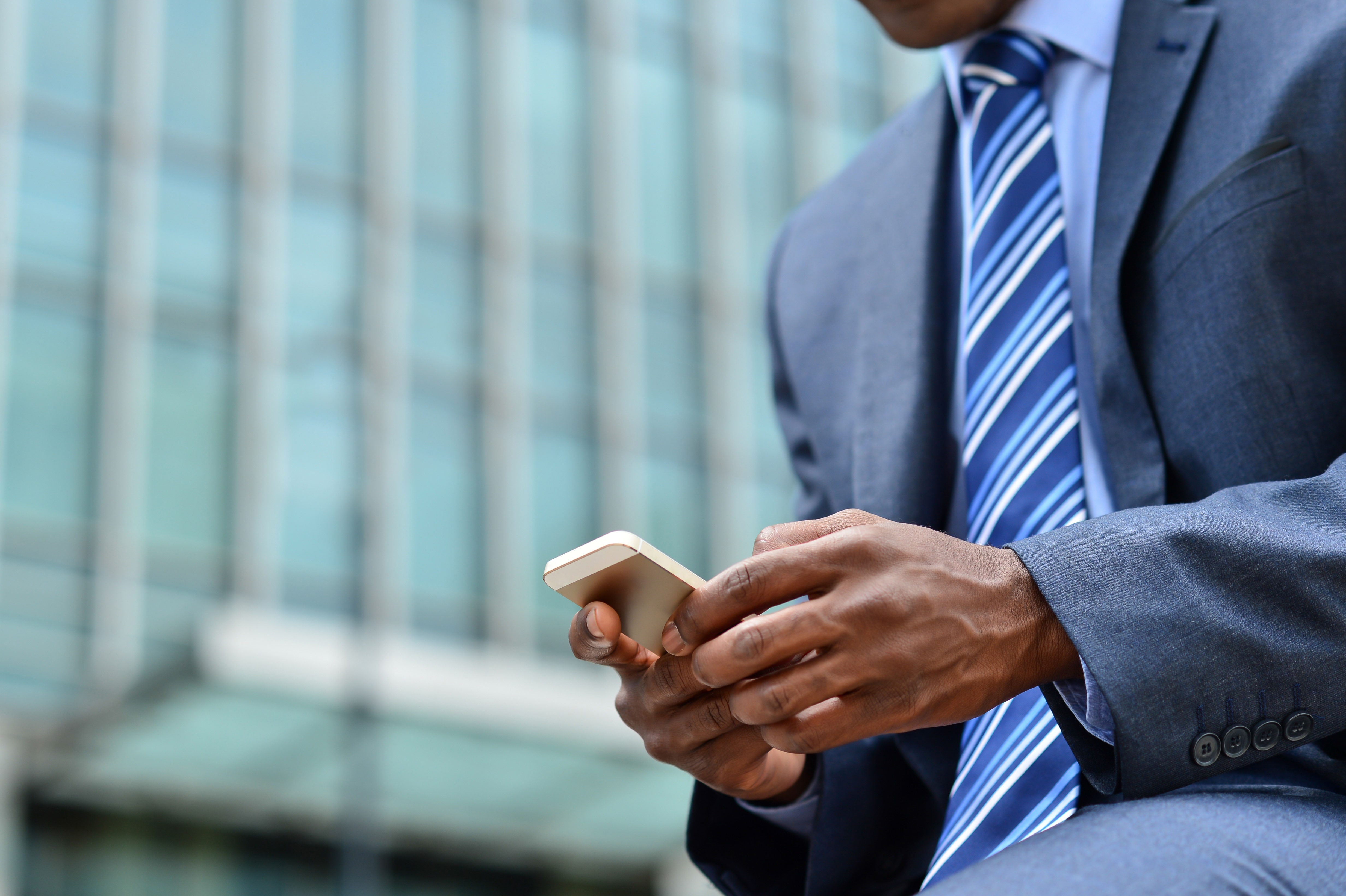Business man in blue tie outside office building texting.jpg